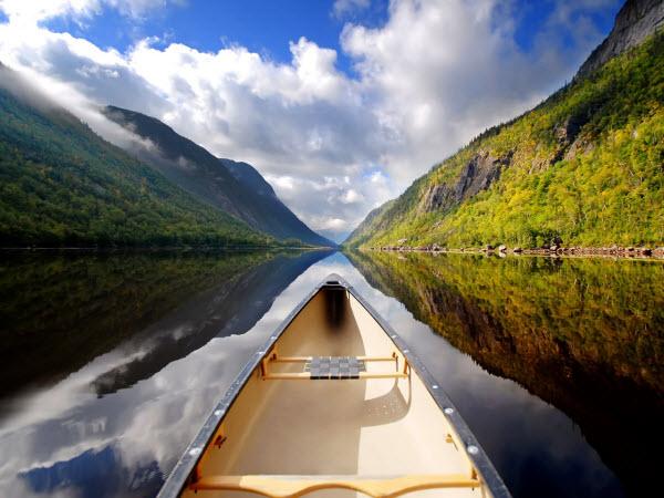 حس لذت بخش قایق سواری در یک رود آرام، در میان کوه ها و جنگل ها با آسمانی تقریبا آرام! عکس تصویر زمینه ای بهتر از این دیده اید؟