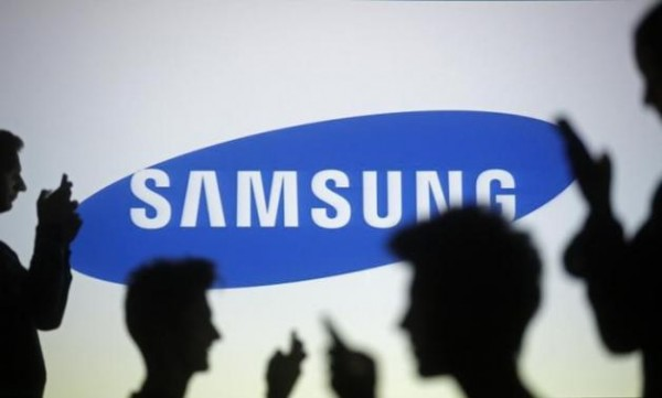 People pose with mobile devices in front of projection of Samsung logo in this picture illustration taken in Zenica